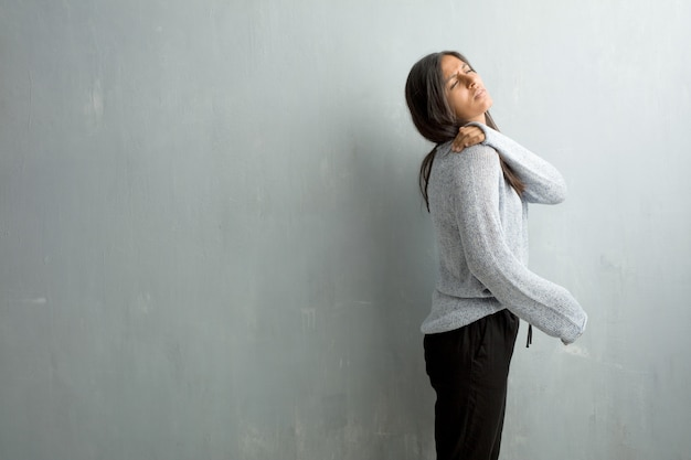 Młoda indyjska kobieta przeciw grunge ścianie z bólem pleców należnym pracować stres