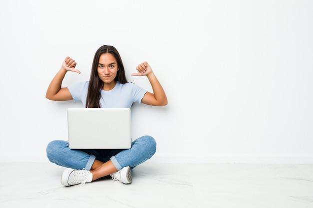 Młoda indyjska kobieta rasy mieszanej siedząca na laptopie czuje się dumna i pewna siebie, przykład do naśladowania.