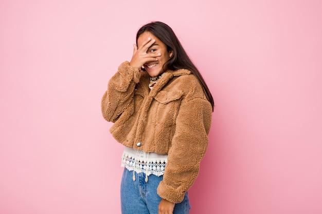 Młoda indyjska kobieta rasy mieszanej, ubrana w krótki płaszcz z owczej skóry, mruga do kamery przez palce, zakłopotana zakrywająca twarz.