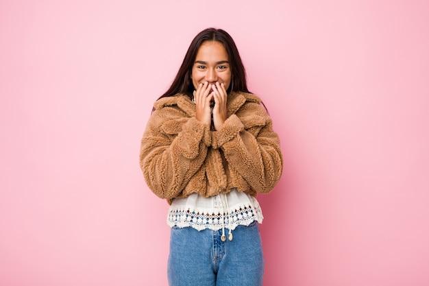 Młoda indyjska kobieta rasy mieszanej, ubrana w krótki płaszcz z owczej skóry, śmiejąca się z czegoś, zakrywająca usta rękami.