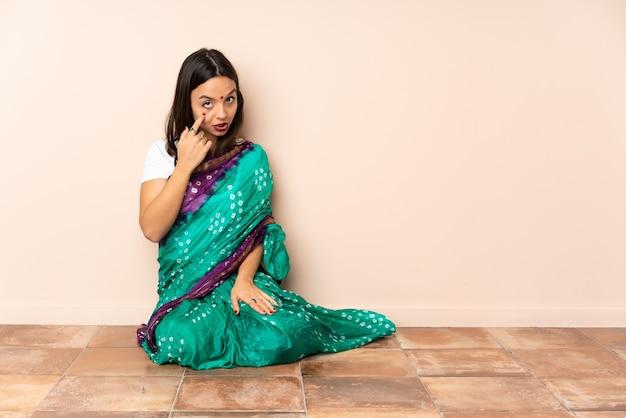 Młoda indyjska kobieta siedzi na podłodze, pokazując coś