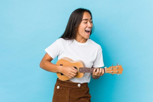 Młoda indyjska kobieta szczęśliwa grając na ukulele na białym tle