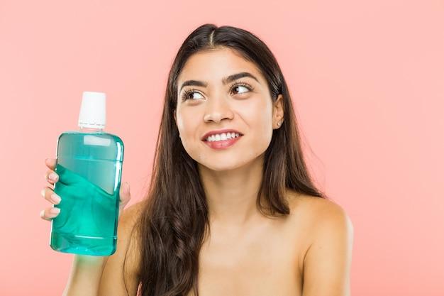 Młoda indyjska kobieta trzyma butelkę do płukania jamy ustnej, uśmiechając się pewnie ze skrzyżowanymi rękami.