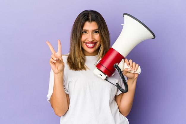 Młoda indyjska kobieta trzyma megafon na białym tle pokazuje numer dwa palcami