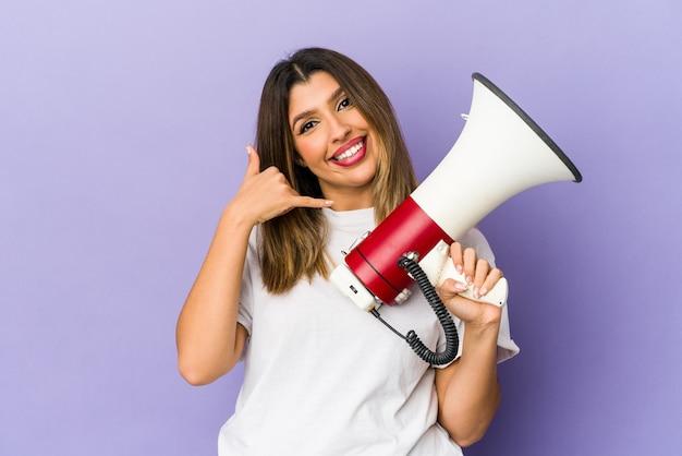 Młoda indyjska kobieta trzyma megafon na białym tle przedstawiający gest rozmowy telefonicznej palcami.