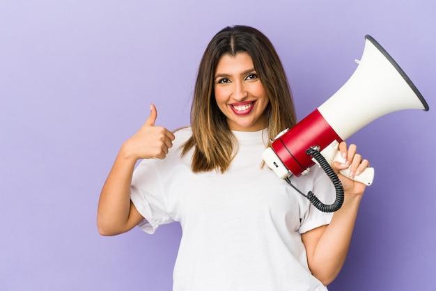 Młoda indyjska kobieta trzyma megafon, uśmiechając się i podnosząc kciuk do góry
