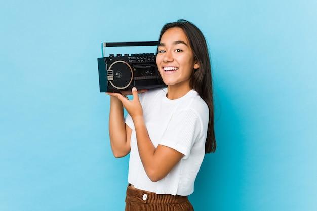 Młoda indyjska kobieta trzyma rocznika kaseta na białym tle