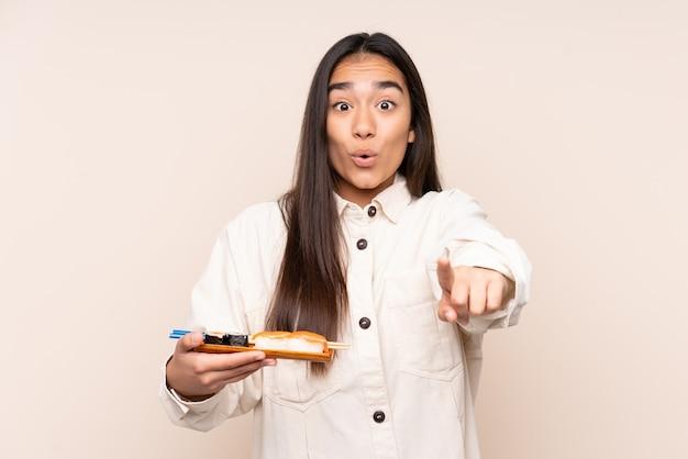 Młoda indyjska kobieta trzyma sushi na białym tle na beż zaskoczony i wskazując przód