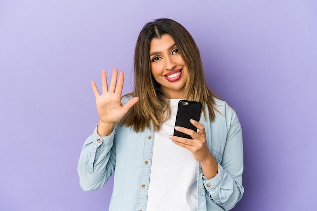 Młoda indyjska kobieta trzyma telefon na białym tle uśmiechnięty wesoły pokazując numer pięć palcami.