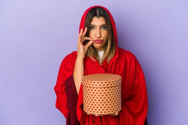 Młoda indyjska kobieta ubrana w hidżab trzyma prezent na walentynki na białym tle z palcami na ustach, zachowując tajemnicę.
