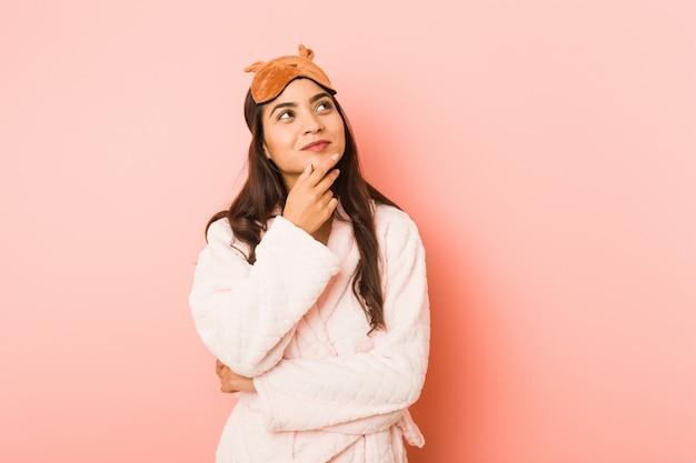 Młoda indyjska kobieta ubrana w piżamę i maskę snu na białym tle patrząc z ukosa z wyrazem wątpliwości i sceptyczny.