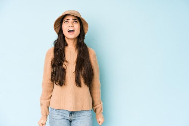 Młoda indyjska kobieta w kapeluszu na białym tle na niebiesko krzyczy bardzo zły, wściekłość, sfrustrowany.