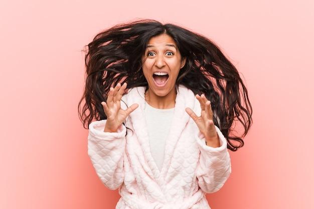Młoda indyjska kobieta w piżamie świętuje zwycięstwo lub sukces