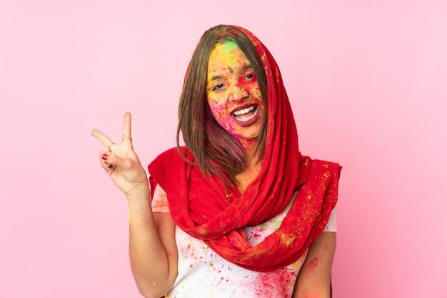 Młoda indyjska kobieta z kolorowymi holi proszkami na jej twarzy na różowej ścianie uśmiecha się znak zwycięstwa i pokazuje