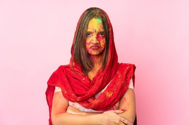 Młoda indyjska kobieta z kolorowymi holi pudruje na twarzy na różowej ścianie z nieszczęśliwym wyrazem twarzy