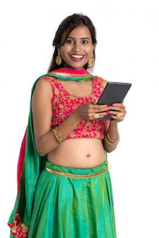 Młoda indyjska tradycyjna dziewczyna używa telefon komórkowego lub smartphone odizolowywających na bielu
