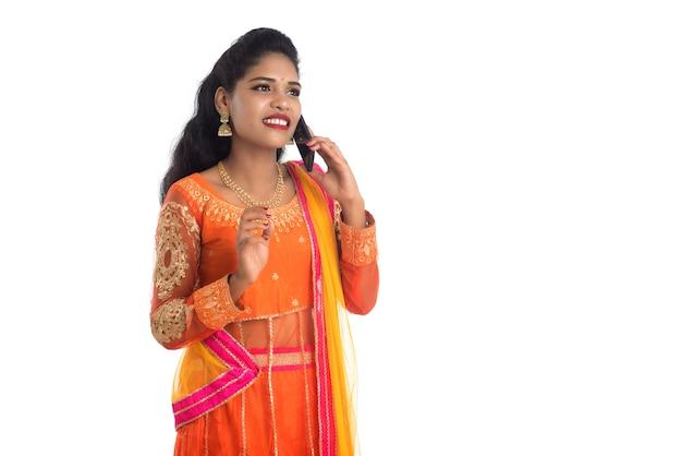 Młoda indyjska tradycyjna dziewczyna za pomocą telefonu komórkowego lub smartfona na białym tle