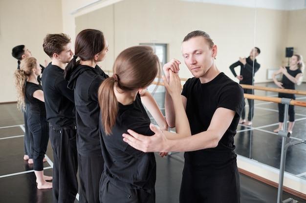 Młoda instruktorka tańca współczesnego baletu stoi obok jednego ze swoich uczniów, pomagając jej w ćwiczeniach na lekcji