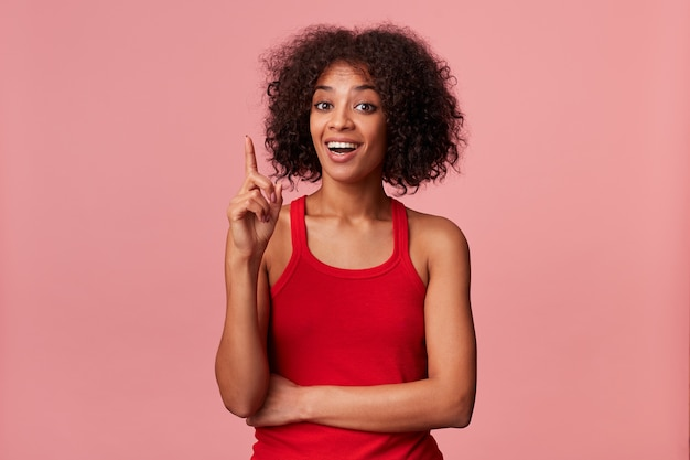 Młoda inteligentna afroamerykanka ubrana w czerwoną koszulkę z ciemnymi kręconymi włosami. uśmiechnięty, pokazuje palec wskazujący do góry, bo mam świetny pomysł. odosobniony.