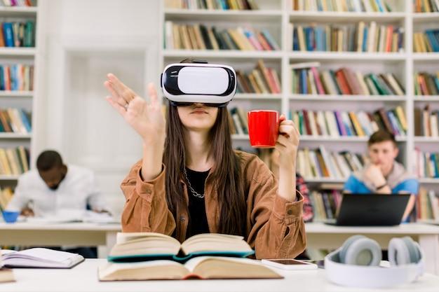 Młoda inteligentna pewna kobieta w przypadkowych ubraniach siedzi w bibliotece i doświadcza nowego urządzenia vr słuchawki do nauki