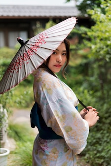 Młoda japonka ubrana w kimono i trzymająca parasolkę