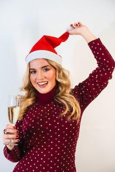 Młoda jasnowłosa dama w czapce mikołaja robi toastowi uroczysty