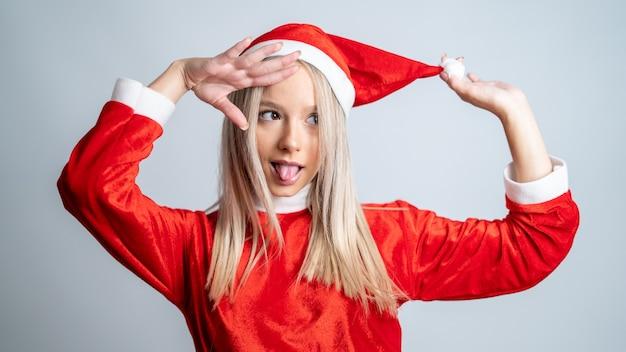 Młoda jasnowłosa kobieta pozuje w stroju miss świętego mikołaja na tle szarej ściany