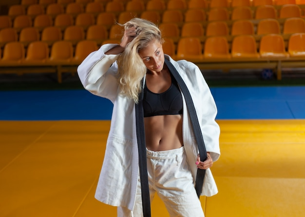 Młoda judoka kobieta w białym kimonie i czarnym pasie pozuje w hali sportowej