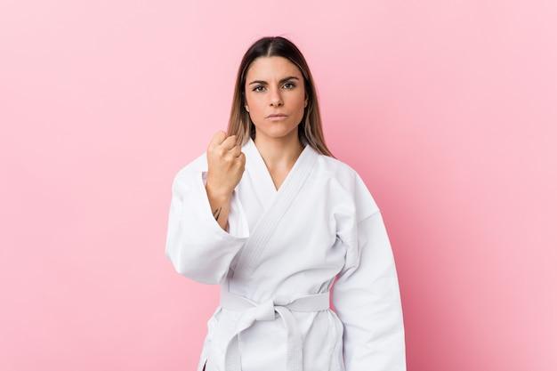 Młoda karate kobieta pokazuje pięść, agresywny wyraz twarzy.