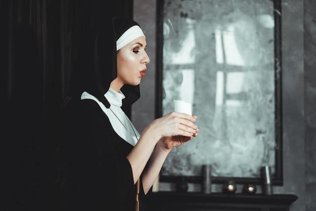 Młoda katolicka zakonnica trzyma w rękach świecę. zdjęcie na czarnym tle. widok z boku.