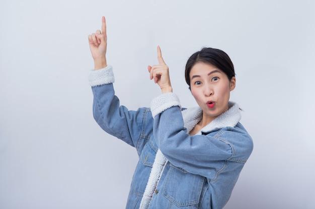 Młoda kaukaska azjatycka uśmiechnięta kobieta wskazuje na białym copyspace tle dla produktu, biznesu i reklamuje pojęcie