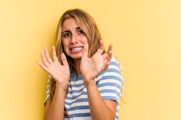 Młoda kaukaska blond kobieta odizolowana na żółtym tle jest zszokowana zbliżającym się niebezpieczeństwem