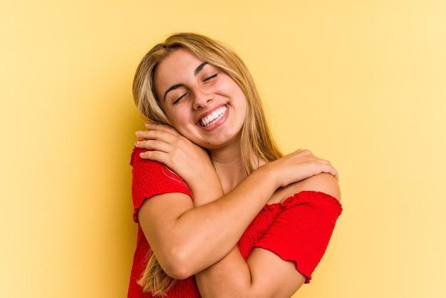 Młoda kaukaska blondynka na białym tle na żółtym tle przytula się, uśmiechając się beztrosko i szczęśliwie.