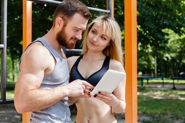 Młoda kaukaska blondynki kobieta i brodaty mężczyzna przegląda internet na białym pastylka komputerze osobistym.