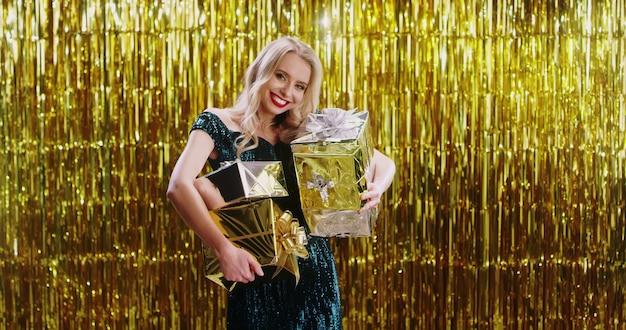 Młoda kaukaska blondynki kobieta w galanteryjnej sukni z wiele prezentami w rękach