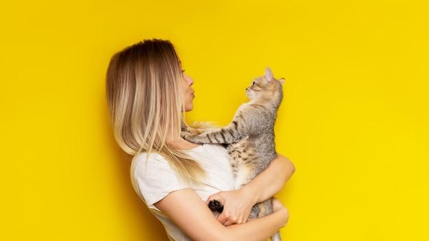 Młoda kaukaska całkiem urocza blondynka trzyma w rękach pręgowanego kota, podziwiając go na jasnej, żółtej ścianie.