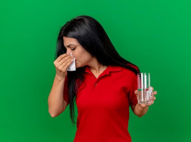 Młoda kaukaska chora dziewczyna trzyma paczkę tabletek szklanką wody i wyciera nos serwetką z zamkniętymi oczami na białym tle na zielonym tle z miejsca na kopię