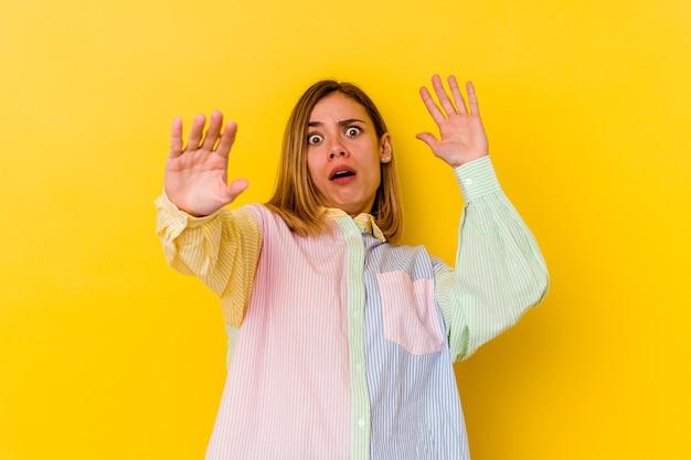 Młoda kaukaska chuda kobieta odizolowana na żółtej ścianie jest w szoku z powodu zbliżającego się niebezpieczeństwa