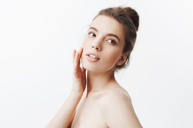 Młoda kaukaska ciemnowłosa studentka o fryzurze kokowej i nagim ciele dotykającym palcami skóry na twarzy, spoglądając na bok ze spokojnym i zrelaksowanym wyrazem twarzy.