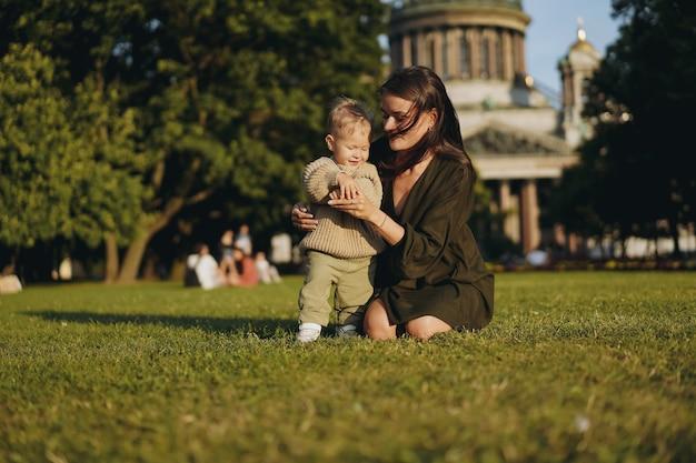 Młoda kaukaska dama matka małego synka siedząca na trawie przed katedrą św