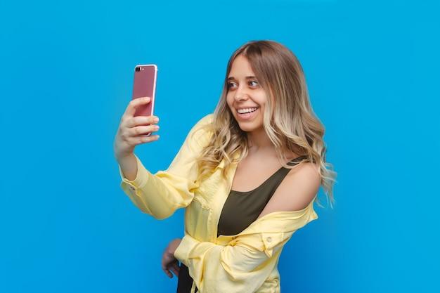 Młoda kaukaska dość uśmiechnięta blondynka w żółtej koszuli robi selfie swoim różowym telefonem komórkowym na jasnej niebieskiej ścianie
