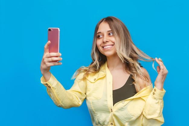 Młoda kaukaska dość uśmiechnięta blondynka w żółtej koszuli robi selfie telefonem komórkowym na jasnej niebieskiej ścianie