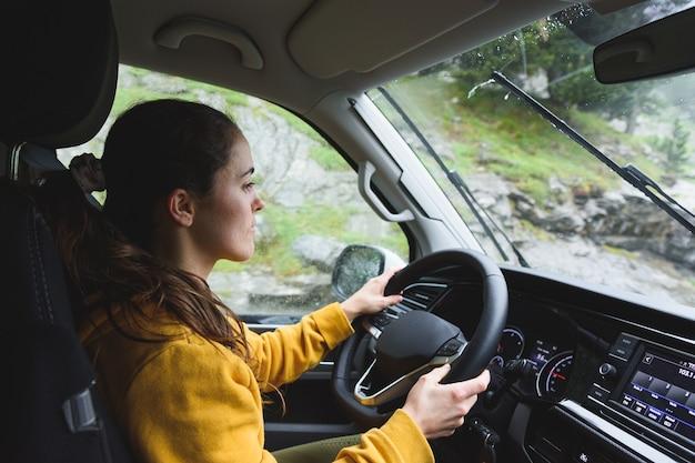 Młoda kaukaska dziewczyna jedzie samochodem kempingowym w dół góry
