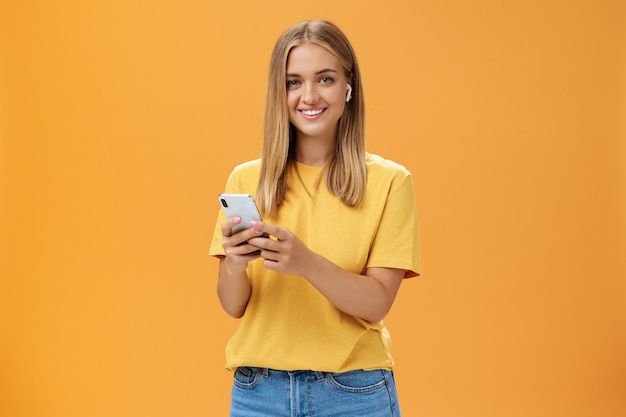 Młoda kaukaska dziewczyna o opalonej skórze i jasnych włosach, korzystająca z bezprzewodowych słuchawek, aby zadzwonić do przyjaciela przez smartfona, trzymając telefon przy klatce piersiowej, uśmiechając się radośnie do kamery, przyzwyczajając się do nowej technologii