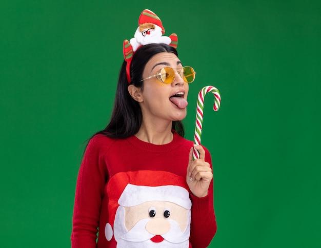 Młoda kaukaska dziewczyna ubrana w opaskę świętego mikołaja i sweter w okularach trzymająca i patrząca na tradycyjną bożonarodzeniową trzcinę cukrową pokazującą język, przygotowującą się do lizania go na białym tle na zielonej ścianie z miejscem na kopię