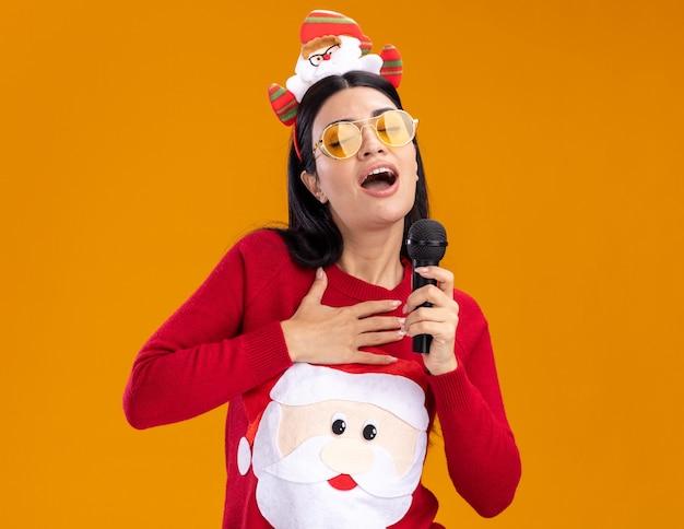 Młoda kaukaska dziewczyna ubrana w opaskę świętego mikołaja i sweter w okularach trzymająca mikrofon przy ustach śpiewająca z zamkniętymi oczami trzymająca rękę na klatce piersiowej odizolowana na pomarańczowej ścianie z kopią przestrzeni