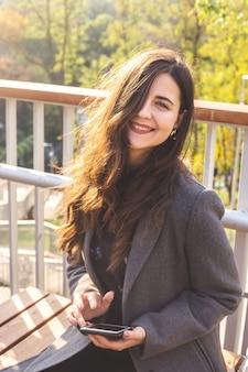 Młoda kaukaska dziewczyna uśmiecha się i trzyma w ręku smartfon.