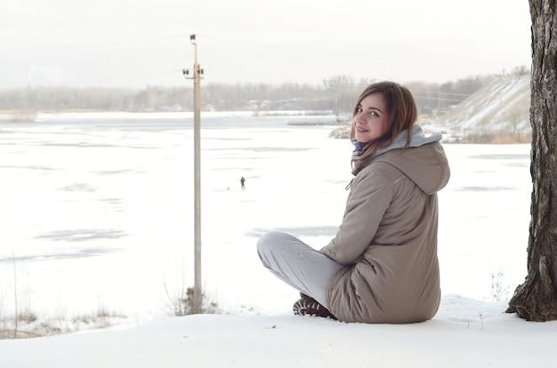 Młoda kaukaska dziewczyna w brązowym płaszczu siedzi w pobliżu urwiska