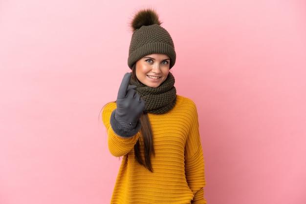 Młoda kaukaska dziewczyna w czapce zimowej na białym tle robi nadchodzący gest