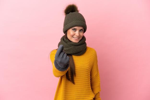 Młoda kaukaska dziewczyna w czapce zimowej na białym tle robi pieniądze gest
